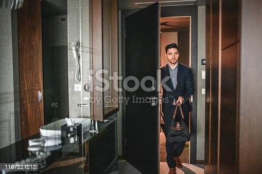 Bearded executive in his late 20s with carry bag entering modern naturally lit hotel room for business travel.