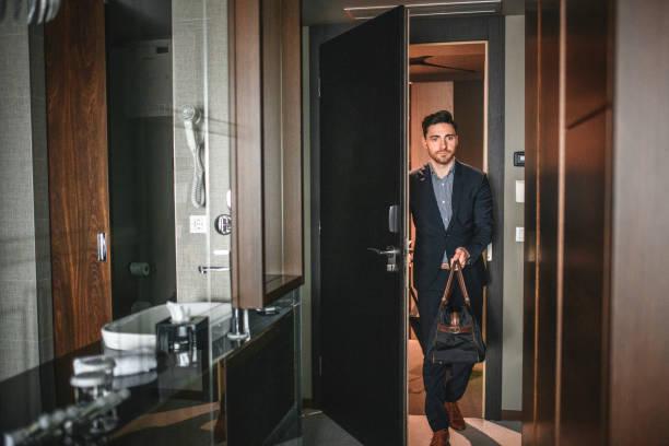 Junger Geschäftsmann mit Gepäck betritt modernes Hotelzimmer – Foto