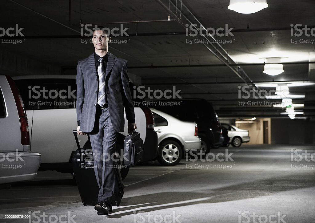 Young businessman with luggage walking through parking garage stock photo