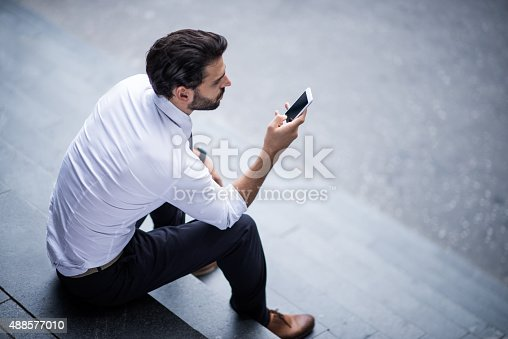 istock Young businessman with smart phone sitting on the stairs 488577010