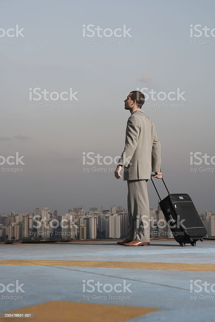 Young businessman with suitcase on rooftop, side view royalty-free stock photo
