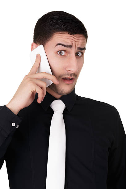 Young Businessman with Surprised Expression on the Phone Young businessman with surprised expression while on the phone bingo caller stock pictures, royalty-free photos & images