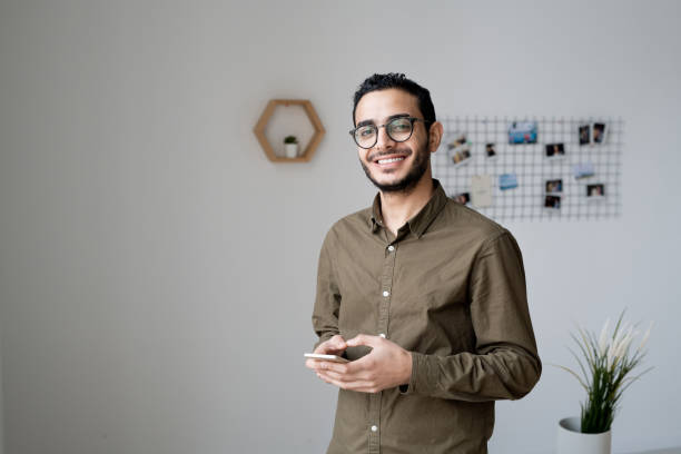 Young businessman with toothy smile using smartphone in front of camera stock photo