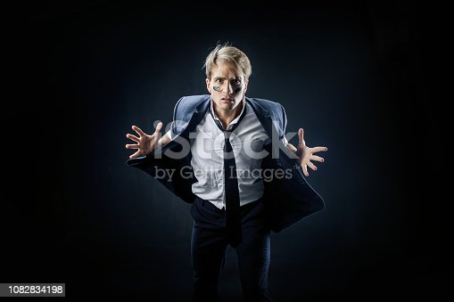 istock Young businessman with war paint on his face. A guy in a business suit was a little stressed 1082834198