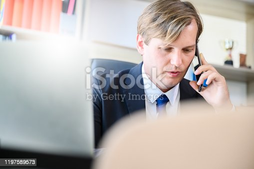 913346608 istock photo Young businessman working at modern office.Man wearing black suit formal and talking mobile phone with laptop 1197589573