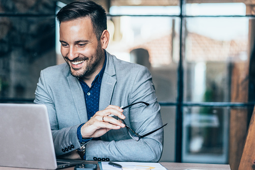 Young cheerful businessman working at office