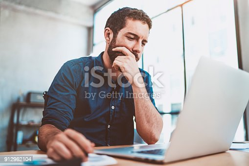 912969272istockphoto Young businessman working at sunny work place on laptop while sitting at the wooden table.Blurred background.Horizontal. 912962104