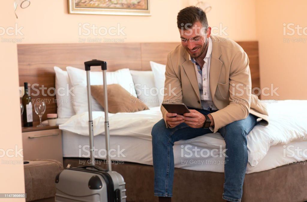 Young businessman working from hotel room on business trip, man...