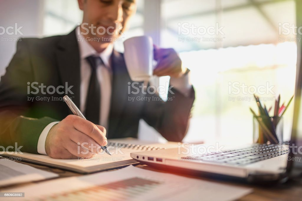 Young Businessman Working In Office And Taking Notes On Notebook royalty-free stock photo