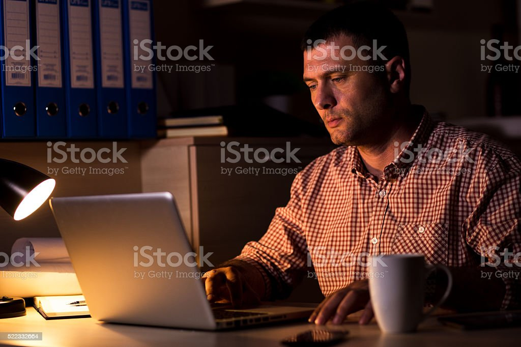 Young businessman working late on laptop stock photo