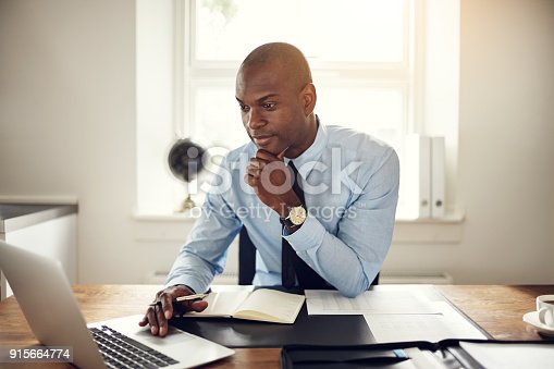 istock Young businessman working on a laptop in an office 915664774