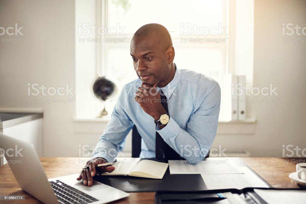 Joven empresario trabajando en un ordenador portátil en una oficina - foto de stock