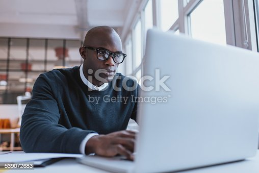 872006502 istock photo Young businessman working on his laptop 539072683