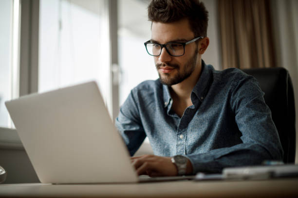 Young businessman working on laptop stock photo