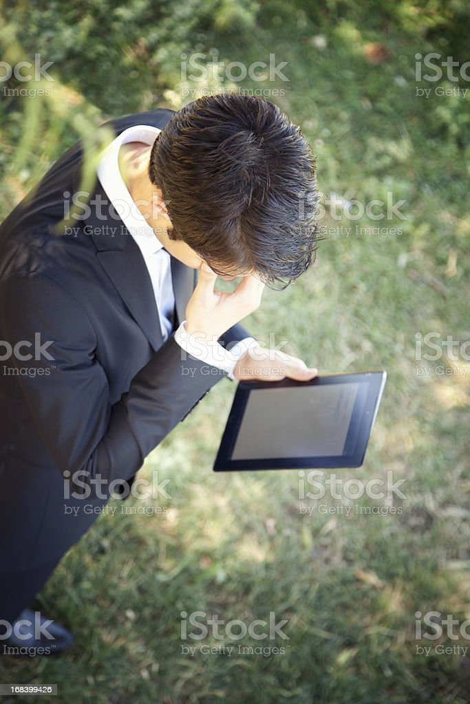 Young businessman working on tablet computer in nature royalty-free stock photo