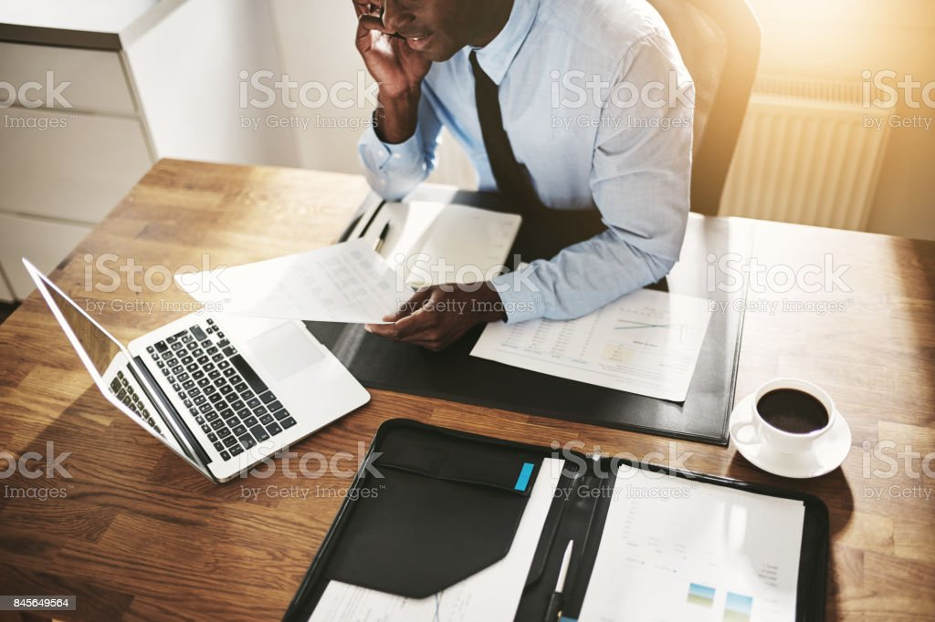 Young businessman working online and reading paperwork over the phone stock photo