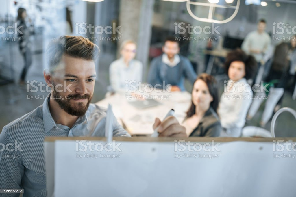 Young businessman writing ideas on whiteboard during a meeting with his colleagues. stock photo