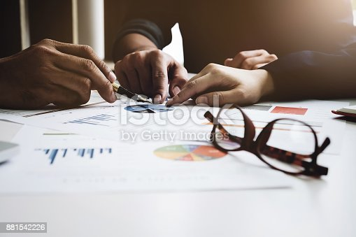 881542122istockphoto Young businessmen holding a pen and partnership  pointing the graph to analyze the marketing plan on wood desk in office. 881542226