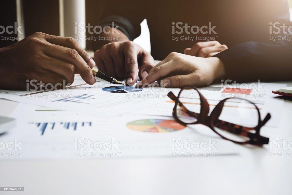 Junge Unternehmer hält einen Stift und Partnerschaft zeigt die Grafik, die Marketing-Plan auf Holz Schreibtisch im Büro zu analysieren. – Foto