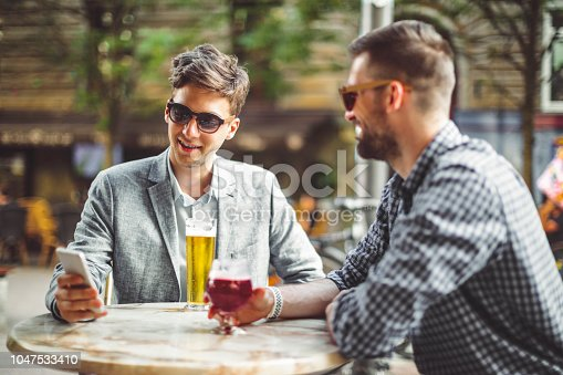 istock Young businessmen in a pub 1047533410