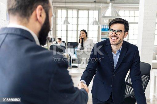 istock Young businessmen in handshake 928369580