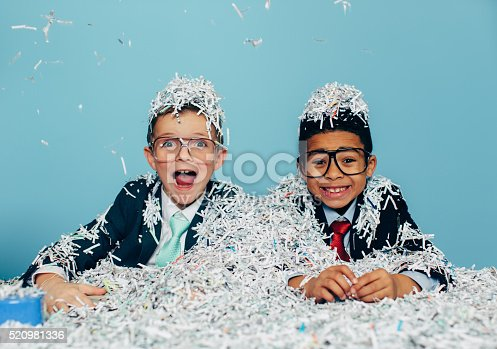 Two young boys and businessman in business attire and glasses sit at an office desk with lots of shredded evidence of their possible business misdeeds. The boys are smiling with as professional work is fun. Or they are throwing an office party. Retro style.