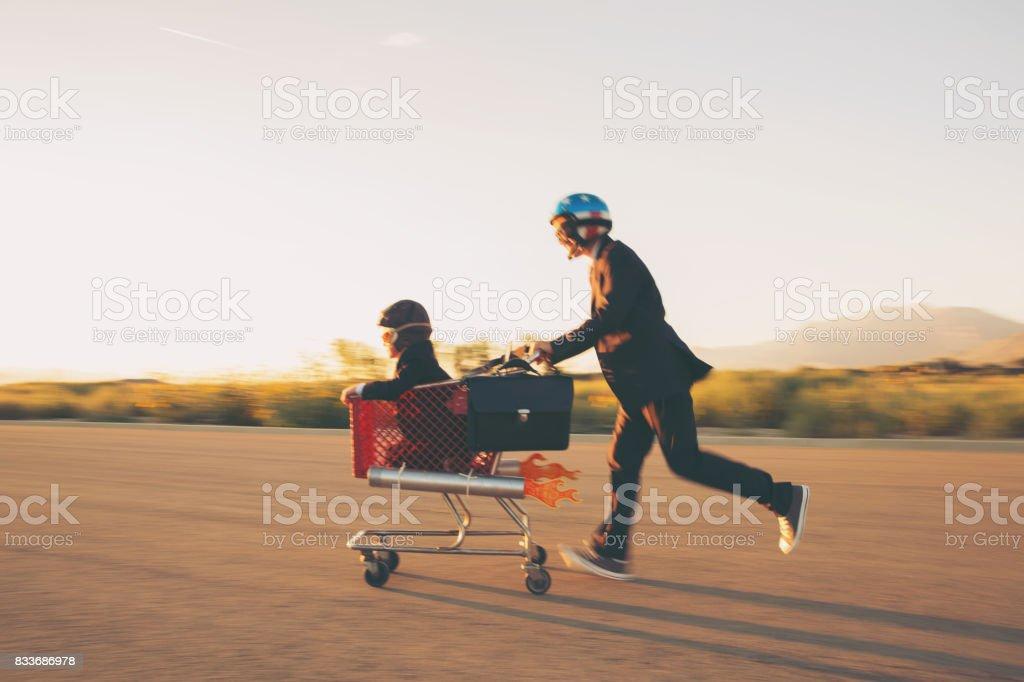 Young Businessmen Racing Rocket Shopping Cart - foto stock