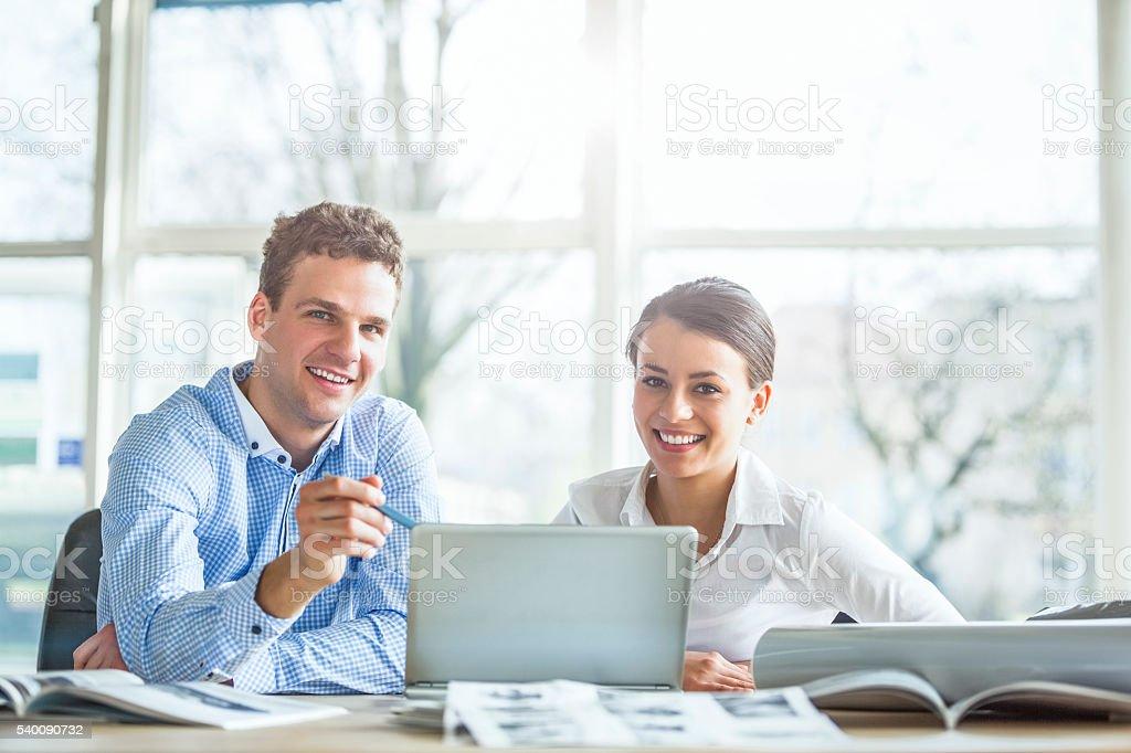 Junge Geschäftsleute diskutieren über Laptop am Schreibtisch im Büro – Foto