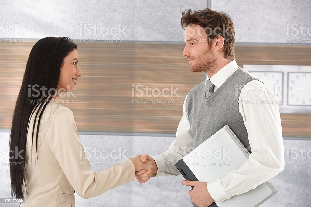 Young businesspeople greeting each other smiling royalty-free stock photo