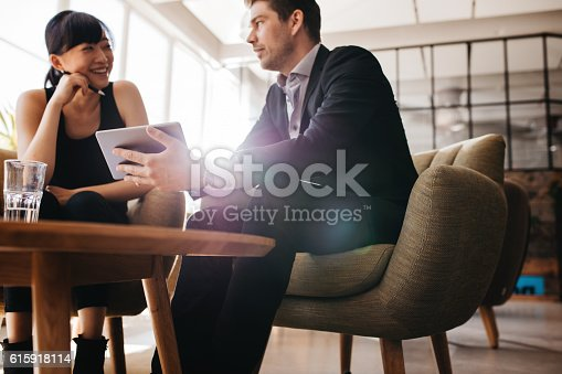 Shot of two young businesspeople using digital tablet in lobby of modern office. Man and woman sitting on foyer working together on tablet computer.