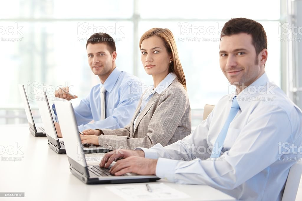 Young businesspeople working on laptop smiling royalty-free stock photo