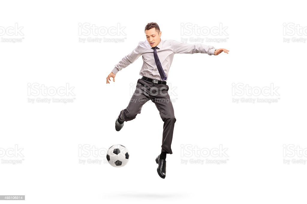 Young businessperson kicking a football stock photo