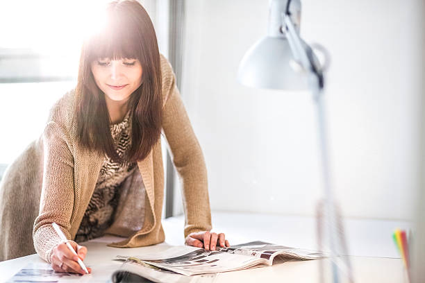 Young businesswoman analyzing brochures at table in office – Foto