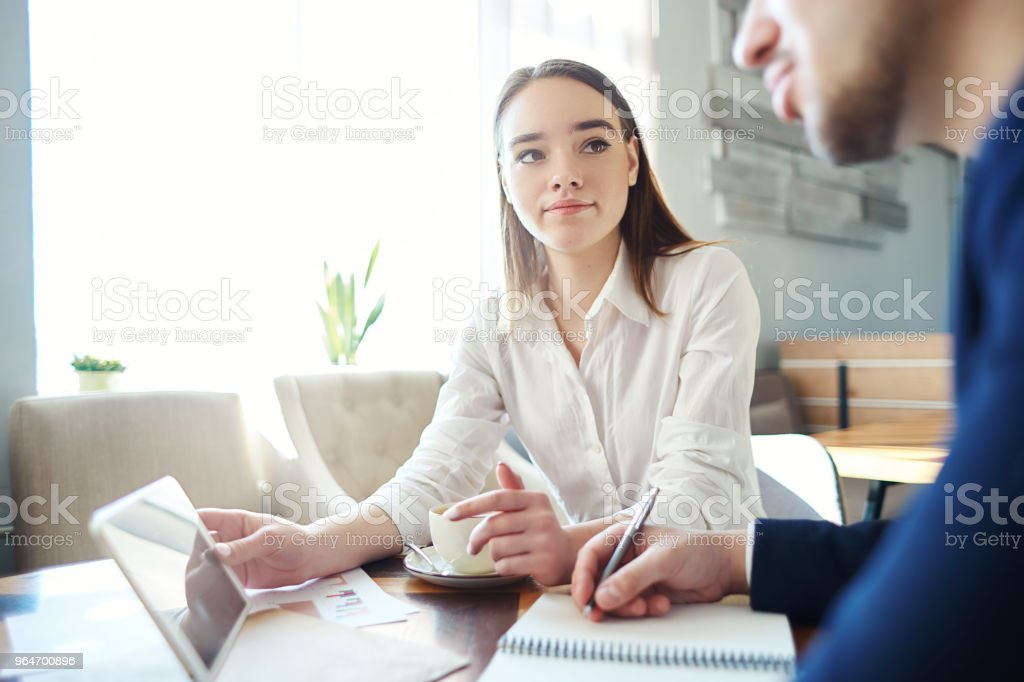 Young businesswoman and her unrecognizable male collague discussing data on tablet computer screen during meeting at cafe. Woman holding tablet and man making notes in his notebook royalty-free stock photo