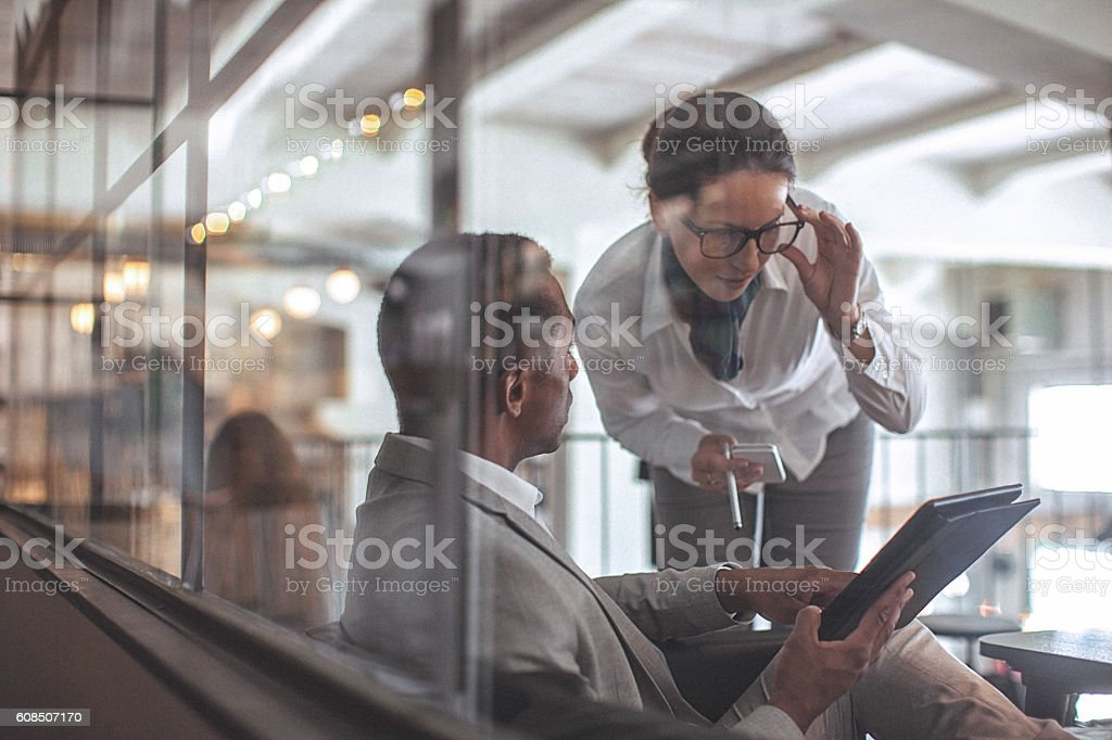 Young businesswoman and man having conversation in modern office space stock photo