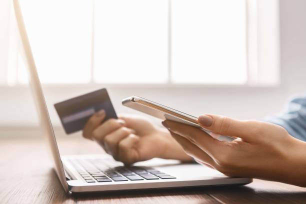 young businesswoman booking tickets online using smartphone and credit card. - wildlife reserve stock pictures, royalty-free photos & images