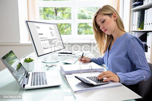 istock Young Businesswoman Calculating Bill In Office 1042650228