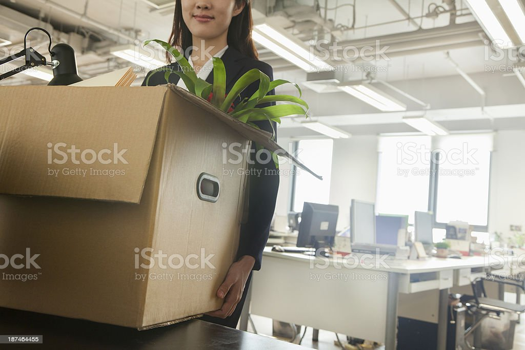 Young businesswoman carrying a box in an office stock photo