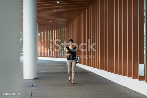A young ethnic businesswoman carries her notes and folders as she checks messages on her phone and walks to a conference. She is on a sidewalk outside a conference center.
