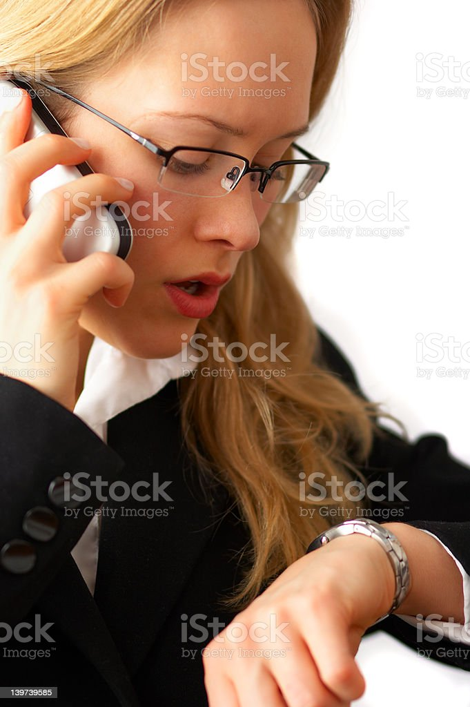 Young businesswoman checking time and making a call royalty-free stock photo