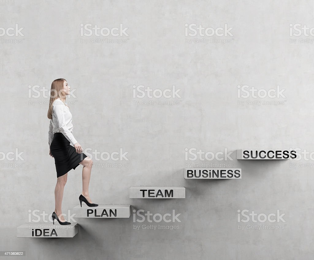 A young businesswoman climbing up stairs stock photo