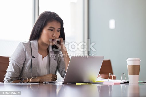 Confident young businesswoman has a serious expression on her face while reading a document on her laptop.