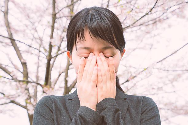 young businesswoman crying under the cherry blossoms - cherry blossoms imagens e fotografias de stock