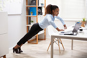 Side View Of A Happy Young Businesswoman Doing Push Up At Workplace