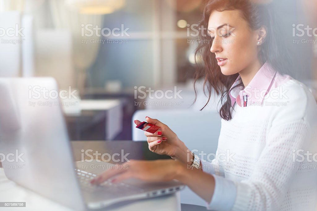 Young businesswoman drinking coffee and using laptop computer in cafe stock photo