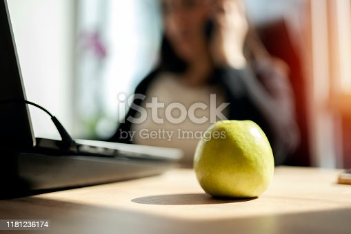 Young businesswoman eating a green apple
