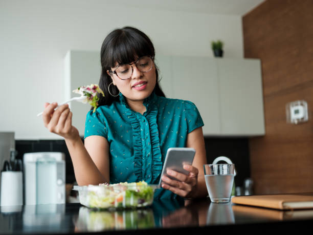 Young businesswoman eating salad in lunch room and using phone stock photo