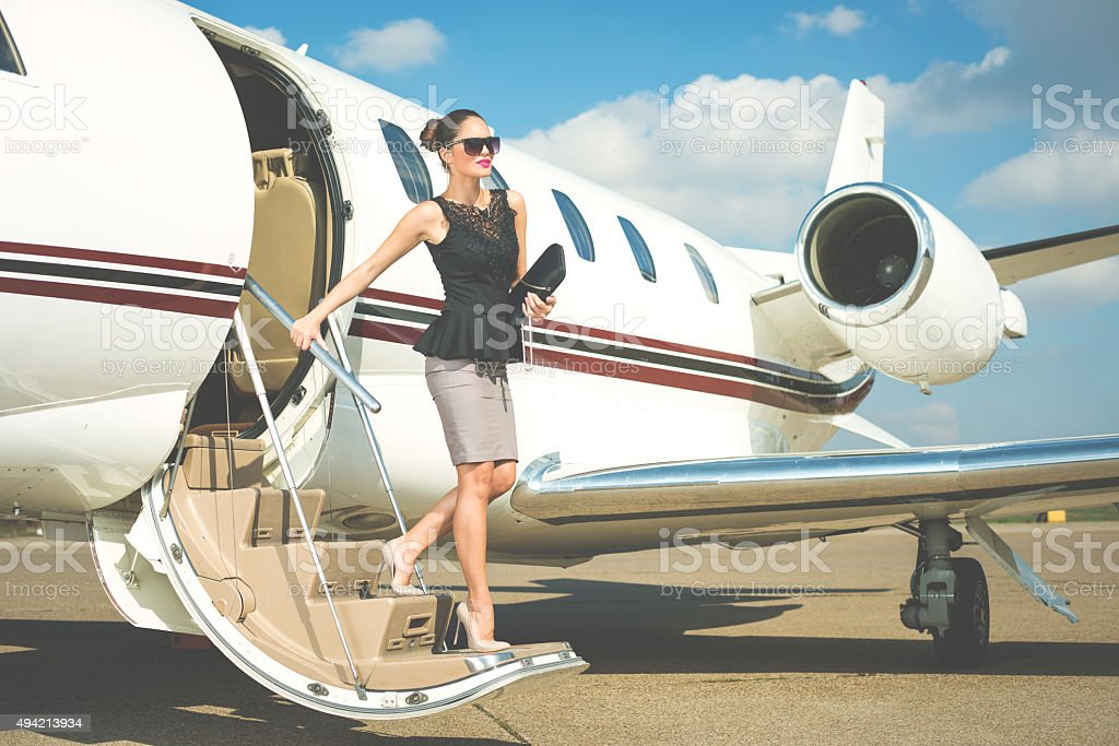 Young businesswoman exiting private aeroplane stock photo