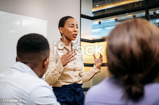 Passionate young woman in her 20s with short hair, discussing with colleagues, African female manger leading her team, ambition, aspiration, empowerment