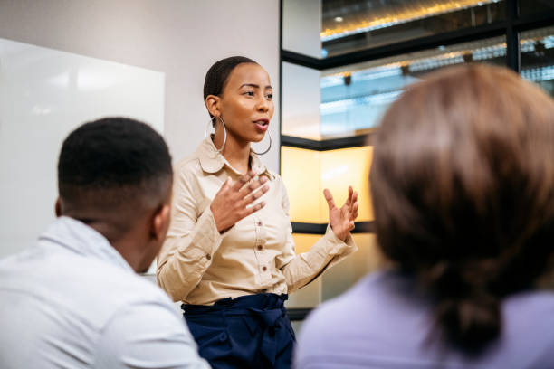 Young businesswoman explaining and gesturing in meeting Passionate young woman in her 20s with short hair, discussing with colleagues, African female manger leading her team, ambition, aspiration, empowerment excited stock pictures, royalty-free photos & images